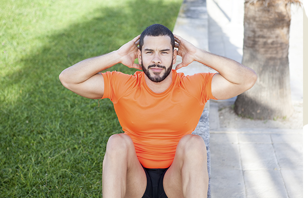 man working out doing a sit up outside on a Saturday