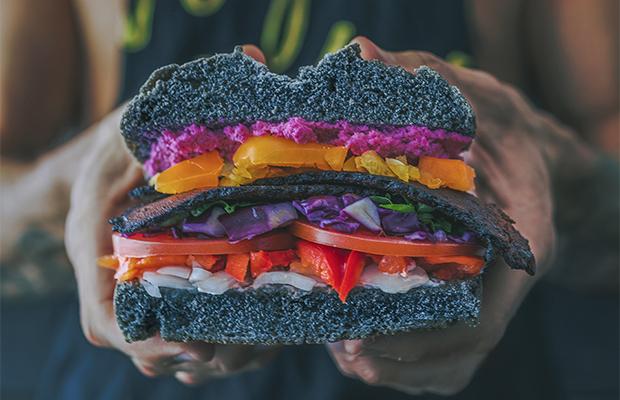 vegan ripped man holding a sandwich for veganuary