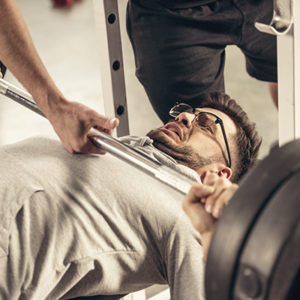 man in the gym being spotted because of a botched bench press