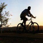 man riding a bike outside at sunset