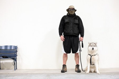 Frank Matrisciano, tough trainer, stands witha mask on and a dog next to him