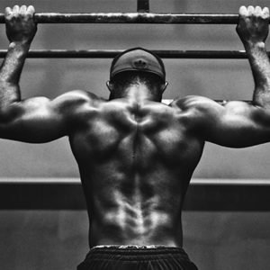 black and white picture of a man doing an overhand pull-up