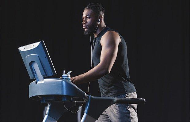 VO2 max man running on a treadmill in a black room