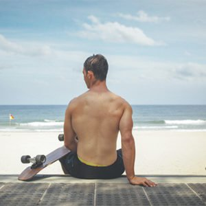 man sitting on the beach looking at the waves with a skate board stay fit