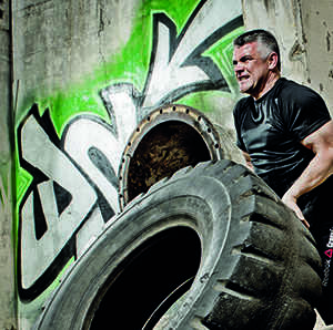 fit belly off man flipping tyres as a workout