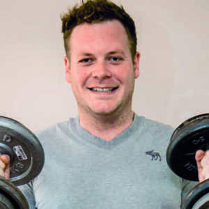 scott malby holding weights and smiling