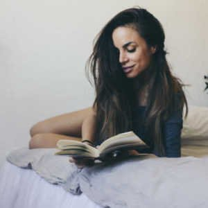 smiling-woman-reading-in-bed