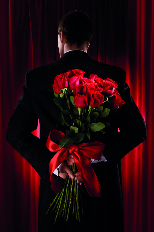 Man in suit holding bouquet of red roses behind his back