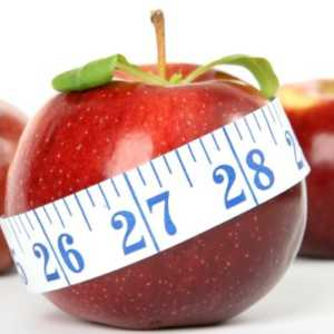 Red apple with tape measure wrapped around