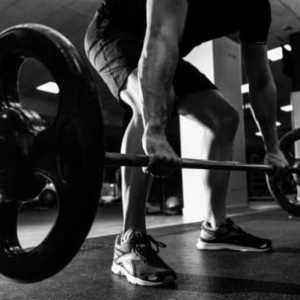 man in a gym doing weightlifting and lifting a barbell