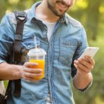man looking at his phone smiling with an orange juice in his other hand