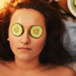 lady lying on a table with cucumbers over her eyes