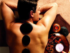 Man receiving a stone back massage in a spa