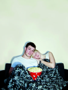 Young couple watching television and eating a huge bowl of fresh buttered popcorn comfortably wrapped in a blanket. The movie might be a bit boring since both of then are sleeping... in the popcorn !!!