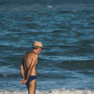 old man standing at a beach in a speedo