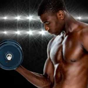 muscular athletic man doing a bicep curl in front of a black background with spotlights