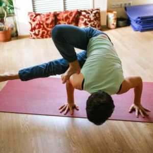 man doing a yoga pose on two hands