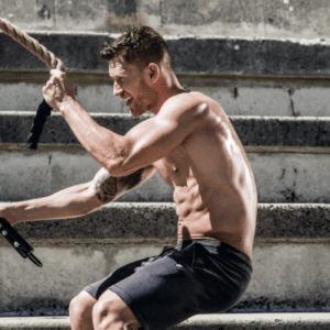 ripped man doing rope exercises in a courtyard