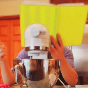someone readin a cookbook in the kitchen