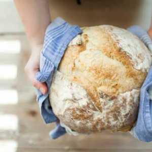 woman holding freshly baked bread loaf