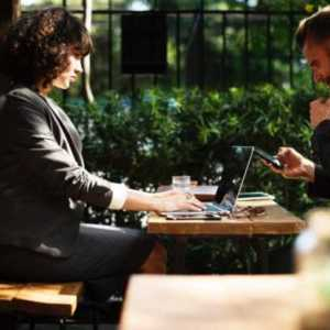 two people sitting at a table working o their laptops