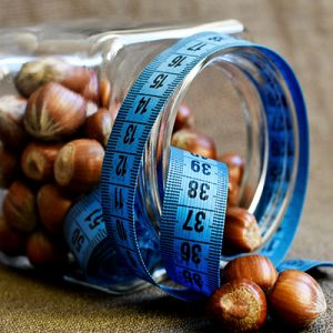 a measuring tape around a jar of nuts someone is consuming for weight loss