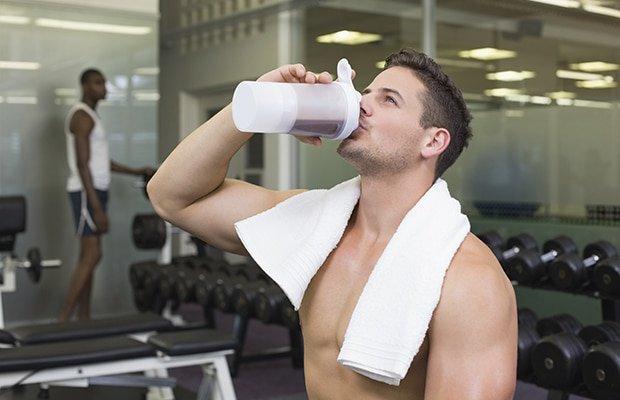 man drinking creatine shirtless in the gym