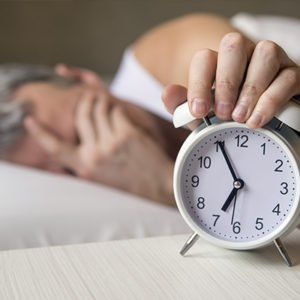 man shutting off his alarm clock