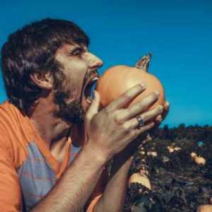man biting into a pumpkin