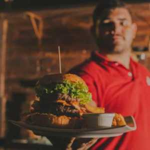 man presenting a massive gourmet burger on a tray