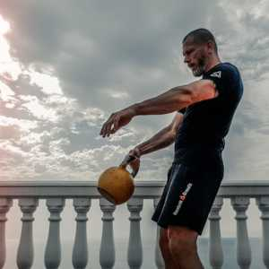 A guy working out with a kettle bell with moody skies