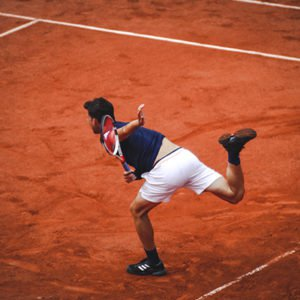 man playing tennis on court sevring ball total-body workout