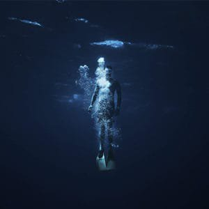 man diving in deep dark blue ocean navy seal