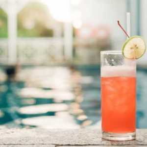 cocktail-at-the-edge-of-the-swimming-pool-red-cocktail-with-an-orange-slice-on-the-background-of-the-swimming-pool-vintage-effect-style-pictures