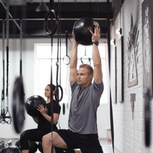 man doing gym work with a medicine ball movement specialists