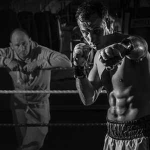 boxer in the ring with his personal trainer watching