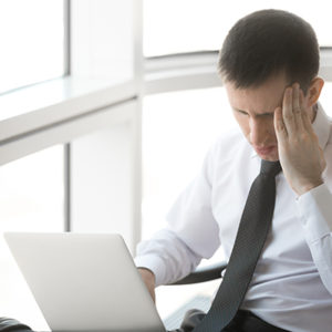 guy sitting with a laptop holding his head because he suffers from migraines