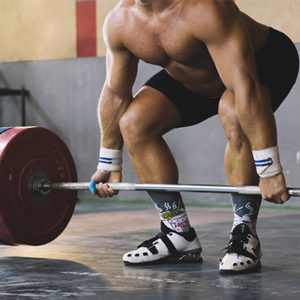 a man gripping a barbell to focus on his grip strength to get stronger