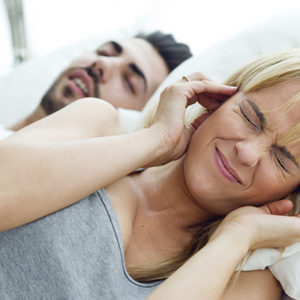 woman closing her ears because wishing she could fix her partners snoring