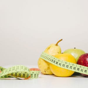 tape measure around fruit for people to eat to lose weight