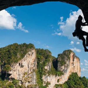 man rock climbing over beautiful ocean thailand holiday