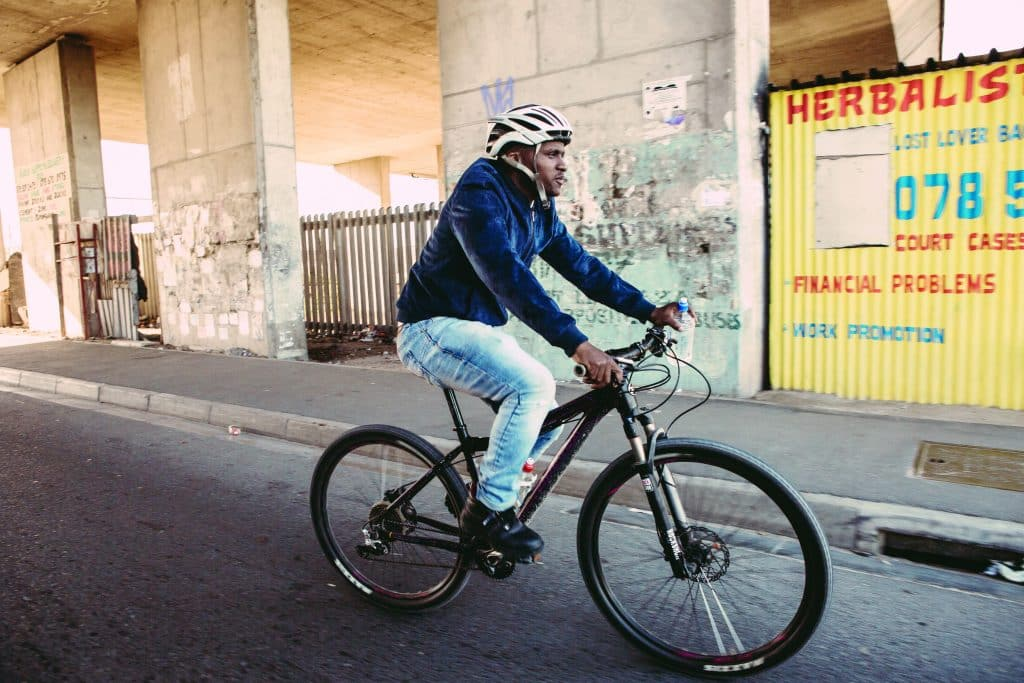 Sizwe Nzima with his township courier business, riding through the streets of Khayelitsa to deliver medication