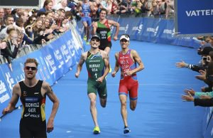 south african triathlete man running to the finish line in a triathlon