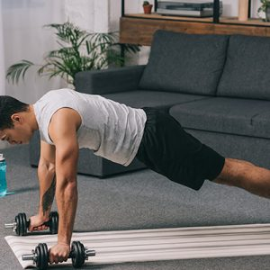 man in plank position trying to build muscle at home