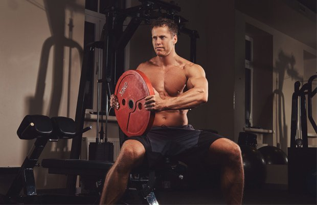 a guy sitting on a bench about to do a weight plate workout