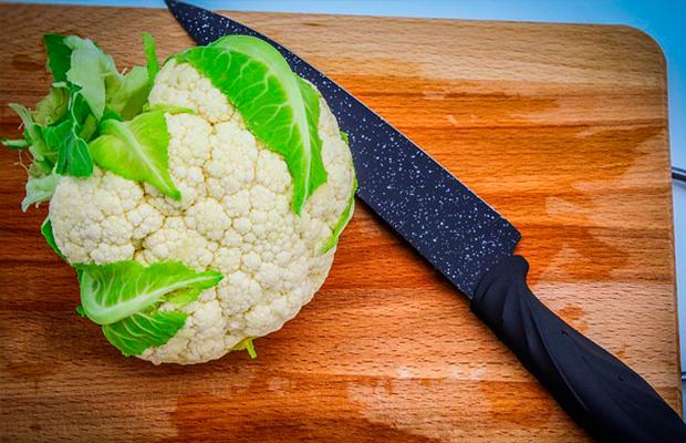 cauliflower on a chopping board next to a knife