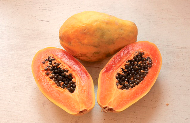 two papayas, one cut in half