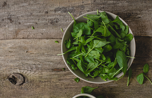 Spinach, which is a source of protein, in a bowl on table
