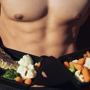 man with abs holding meal prep services